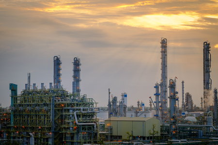 Furnace and gas refinery tower in petrochemical industrial plant on sunset sky background