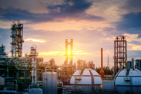 Manufacturing of oil and gas refinery industrial or Petrochemical industry plant on sunset sky background with smoke stacks and gas sphere tanks Redactioneel