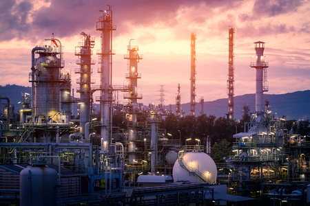 Gas refinery plant on sunset sky background, Manufacturing of petrochemical industrial plant with distillation tower and gas storage sphere tank