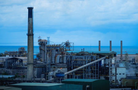 Factory building of petroleum industrial plant with sea and sky background