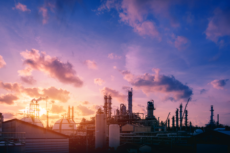 Factory of petroleum industrial plant with oil and gas refinery tower on sunset sky background