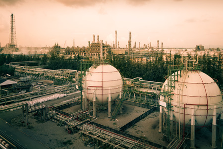 Gas storage sphere tanks in oil and gas refinery industry with pipeline, Orange sky sunset with sphere tanks in petroleum industrial estate