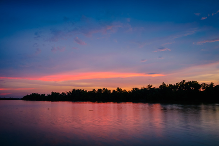 Sunset sky view with silhouette trees at river side
