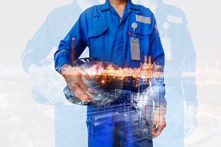 Technician stand hand holding safety helmet with blue uniform with double exposure oil and gas refinery industrial, Workers in petroleum industrial concept