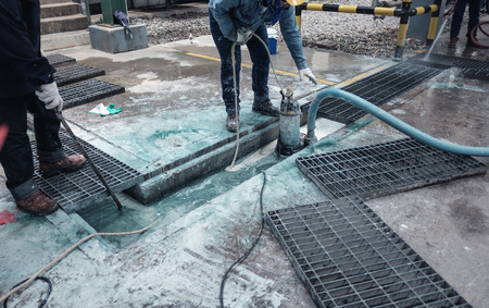 Contractor cleaning chemical drain in industrial plant Stockfoto