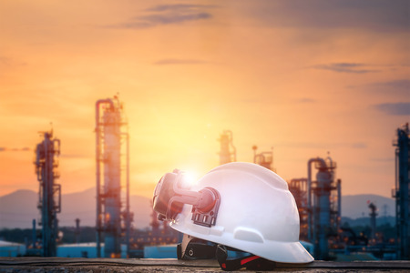 White safety helmet with earmuffs on blurred industrial plant background with sunset , industrial work concept