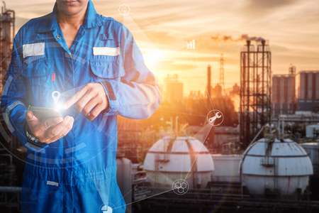 Asia engineer stand holding hand touch of smart phone on oil and gas refinery plant background, Engineer planning work concept, Professional technician monitoring of petrochemical industry plant
