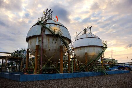 Gas storage sphere tanks on sunset sky background