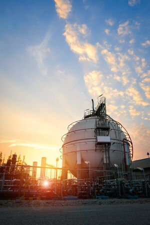 Gas storage sphere tanks in oil and gas refinery industrial plant with sunset sky background