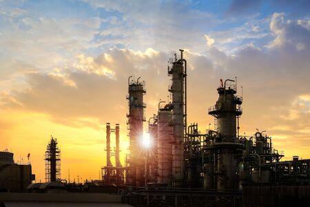 Olie- en gasraffinaderij of petrochemische industrie op de achtergrond van de hemelzonsondergang, fabriek 's avonds, productie van aardolie-industriële installaties Stockfoto