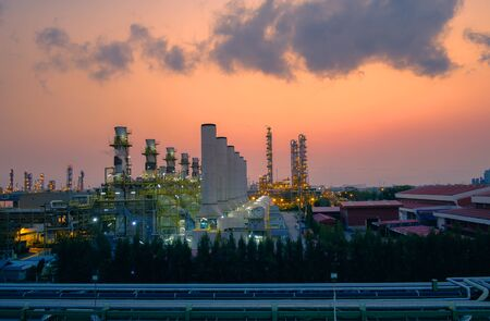 Factory of oil and gas refinery industrial plant with sunrise sky background, Pipeline of petrochemical industry, Smoke stacks of power plant Stockfoto