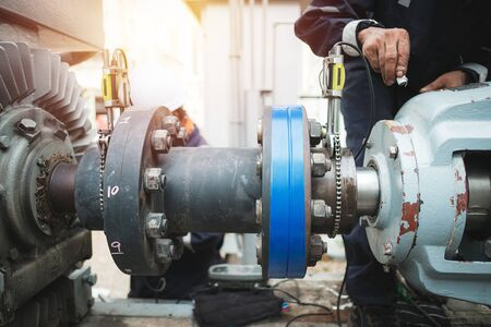 Technician inspector alignment pump  and electric motor, Repairing work in factory concept Фото со стока