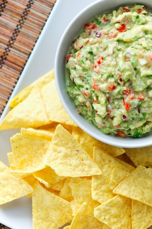 guacamole: Top view of a guacamole and chips on a plate.  Stock Photo