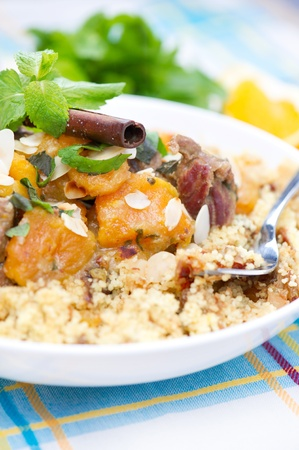 A plate with delicious looking cous cous with lamb meat, apricots, almonds, raisins, dates, cinnamon and mint.  Stock Photo