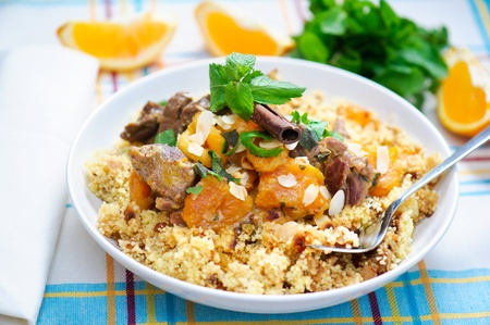 raisins: A plate with delicious looking cous cous with lamb meat, apricots, almonds, raisins, dates, cinnamon and mint.  Stock Photo