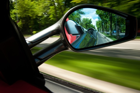exotic car: Rear view mirror panning from inside a speeding exotic car.