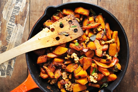 skillet: Top view of a freshly cooked skillet full of balsamic vinegar glazed pumpkin with walnuts and chili