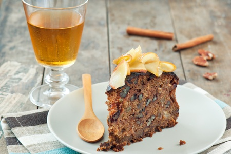 A slice of homemade apple cake with a glass of cider in the background, on a wooden table.  photo