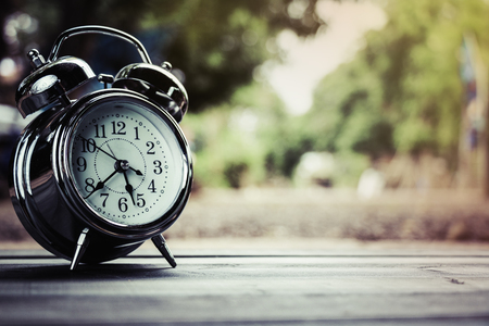the old clock on the old wooden floor with blur background of nature Stock Photo
