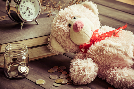 white wood floor: a teddy bear on the wooden floor with some money coins in a glass bottle and a clock on the books still life style