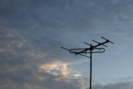 Television antenna on the roof top with evening sky background