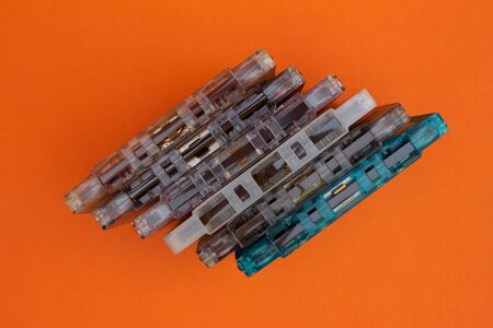 Top view of audio cassettes stacked together. Obsolete music technology and devices