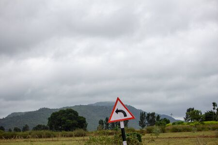 Indian road sign indicating curve ahead, Hasanur, Tamil Nadu, India
