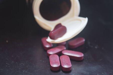 Red coloured pills spilling out of a pill bottle.