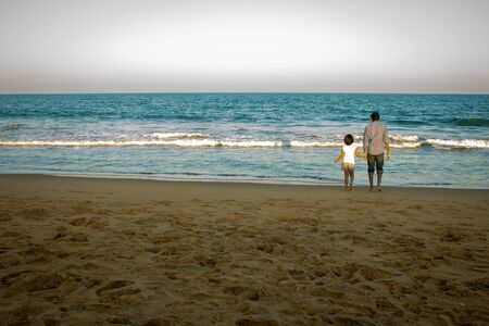 Father and daughter enjoying their holiday in a beach. Beach scene with adult and kid holding hands and enjoying the waves.