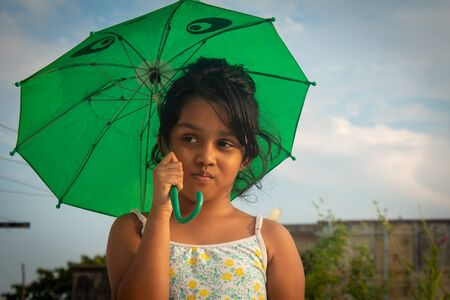 Cute little girl with umbrella on a sunny day