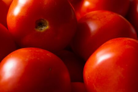 Close view of red tomatoes in heap. Fresh red tomato fruit for food background, food closeup.