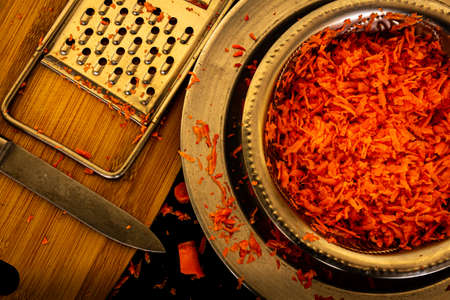 View of grated carrots in a bowl along with the grater and knife