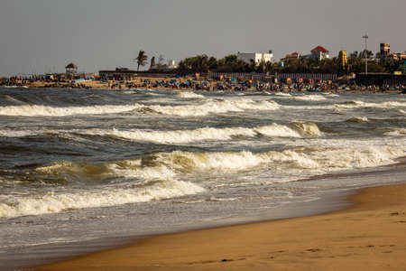 Kovalam, Tamil Nadu, India - February 04 2021: Scenic view of the waves and people having fun along the Kovalam beach, Chennai, India.