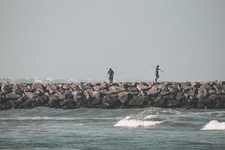 Kovalam, Tamil Nadu, India - February 04 2021: People fishing over the rocks along the Kovalam beach, Chennai, India. Redakční