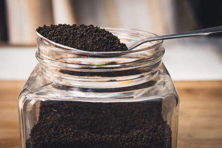 View of finest tea powder in a spoon placed over a glass container. Common dust tea used in India Reklamní fotografie