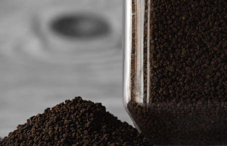 View of finest tea powder in a heap next to a glass container. Common dust tea used in India