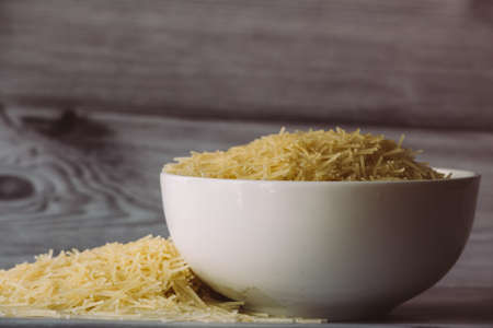 Vermicelli in a bowl and heap of them next to bowl. View of pasta vermicelli
