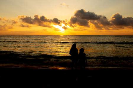 Kids in silhouette watching the sunrise in Marina Beach, Chennai, India