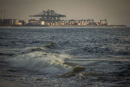 Scenic view of the waves of the Bay of Bengal along Marina Beach with port in background, Chennai, India