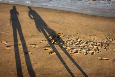 Shadow of a couple over the beach sand in Mahabalipuram. Couple's shadow over the seashore