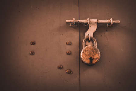 Rusted old lock on a wooden door latch for safety