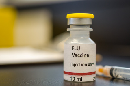 Flu vaccine vial. The label is created for photography purpose only