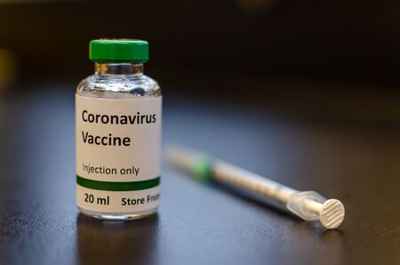 Coronavirus vaccine vial with syringe. The label is created for photography purpose only