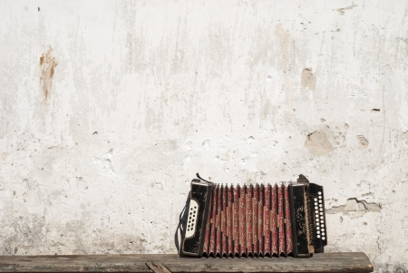 portable audio: wall and accordion on the bench background