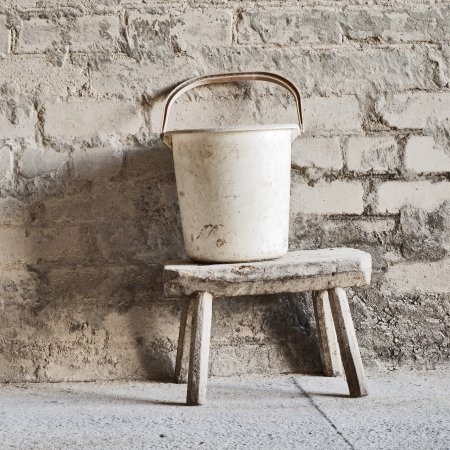 grunge wall, white bucket on the wooden seat background at the mill Stock Photo - 16719554