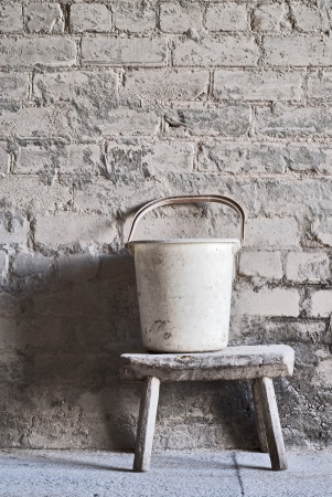 grunge wall, white plastic bucket on the wooden seat background at the mill warehouse Stock Photo - 16719697