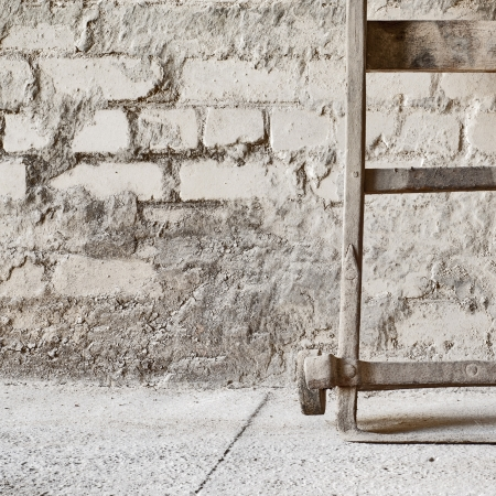grunge wall, vintage two wheels barrow for carrying grain sacks background  Stock Photo - 16719552