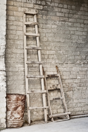 grunge wall, ladder, old barrel, vintage wheelbarrow for carrying bags of grain background
