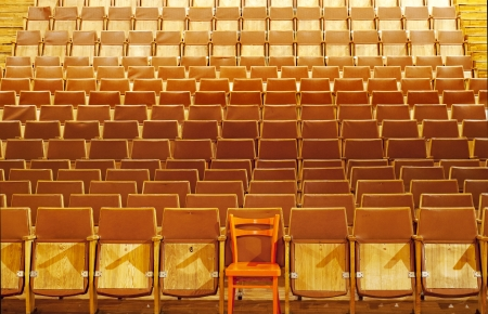 Theater seats, front side, one red seat, seventh place, first row Stock Photo