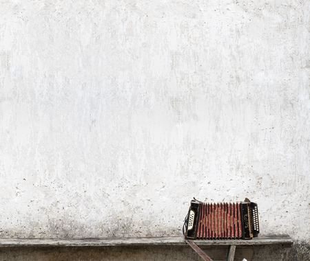 accordion on the bench near the wall background